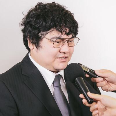 「売却問題で報道陣に取材を受ける男性」の写真素材