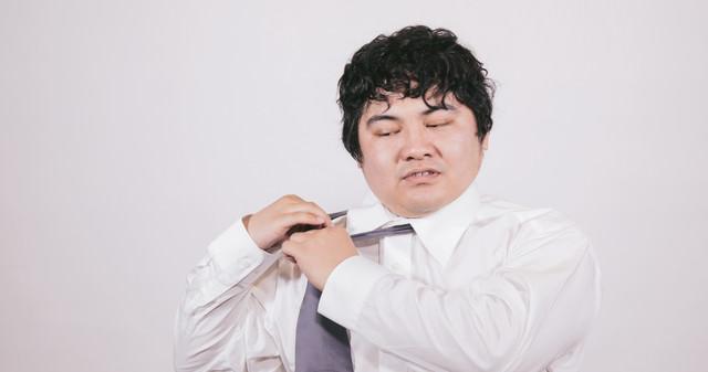 ネクタイを外すサラリーマンの写真