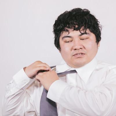 「ネクタイを外すサラリーマン」の写真素材