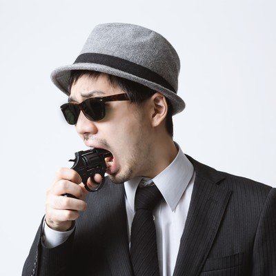 「拳銃を口に突っ込むエージェント」の写真素材