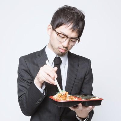 「のり弁当を食べる会社員」の写真素材