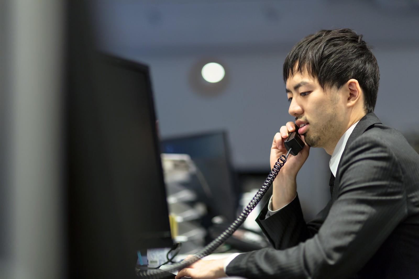「取引先に電話を掛けるオフィスのサラリーマン」の写真[モデル:ひろゆき]