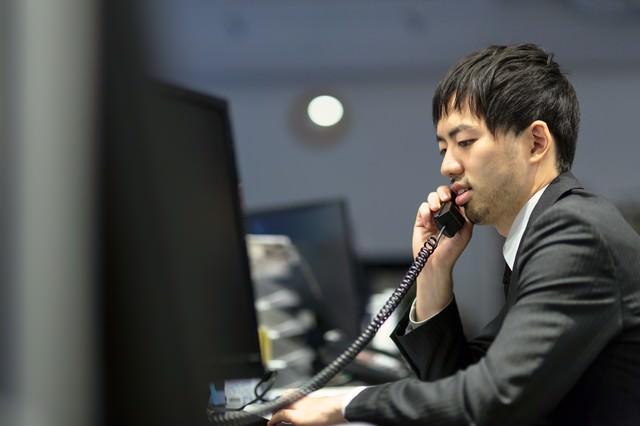 取引先に電話を掛けるオフィスのサラリーマンの写真