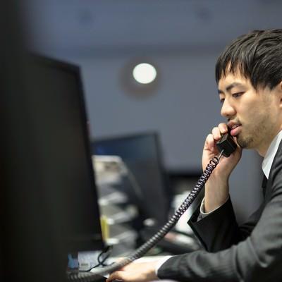 「取引先に電話を掛けるオフィスのサラリーマン」の写真素材