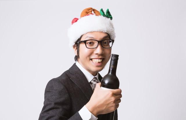 サンタ帽を被ってワインボトルを握るサラリーマンの写真