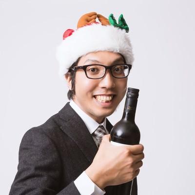 「サンタ帽を被ってワインボトルを握るサラリーマン」の写真素材