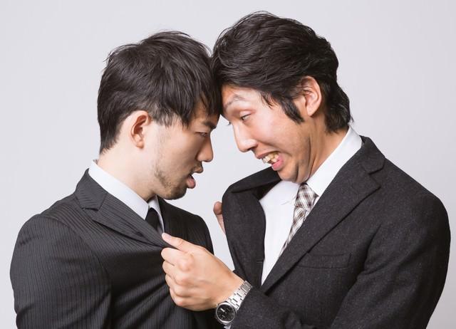 白目をむいて掴み合いの喧嘩をするサラリーマンの写真