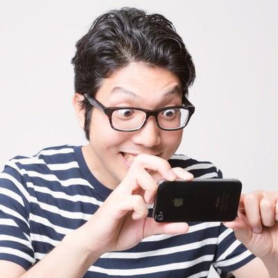 「スマホでガチ撮りする男性」の写真素材