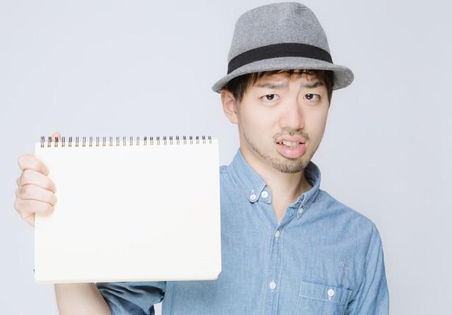 ノートを見せるハットをかぶった男性の写真
