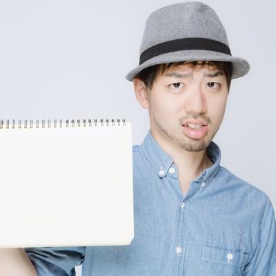 「ノートを見せるハットをかぶった男性」の写真素材