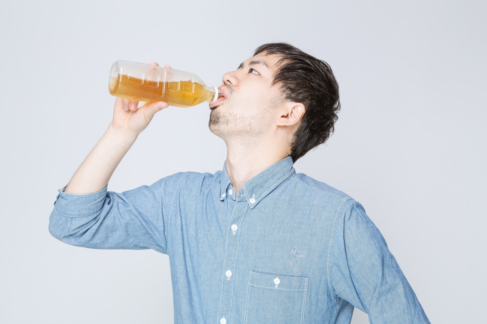 「お茶をぐびぐび飲む男性」の写真[モデル:ひろゆき]