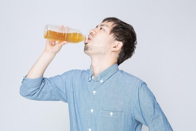 お茶をぐびぐび飲む男性の写真