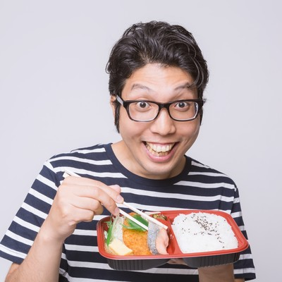 喜んでお弁当を食べる男性の写真