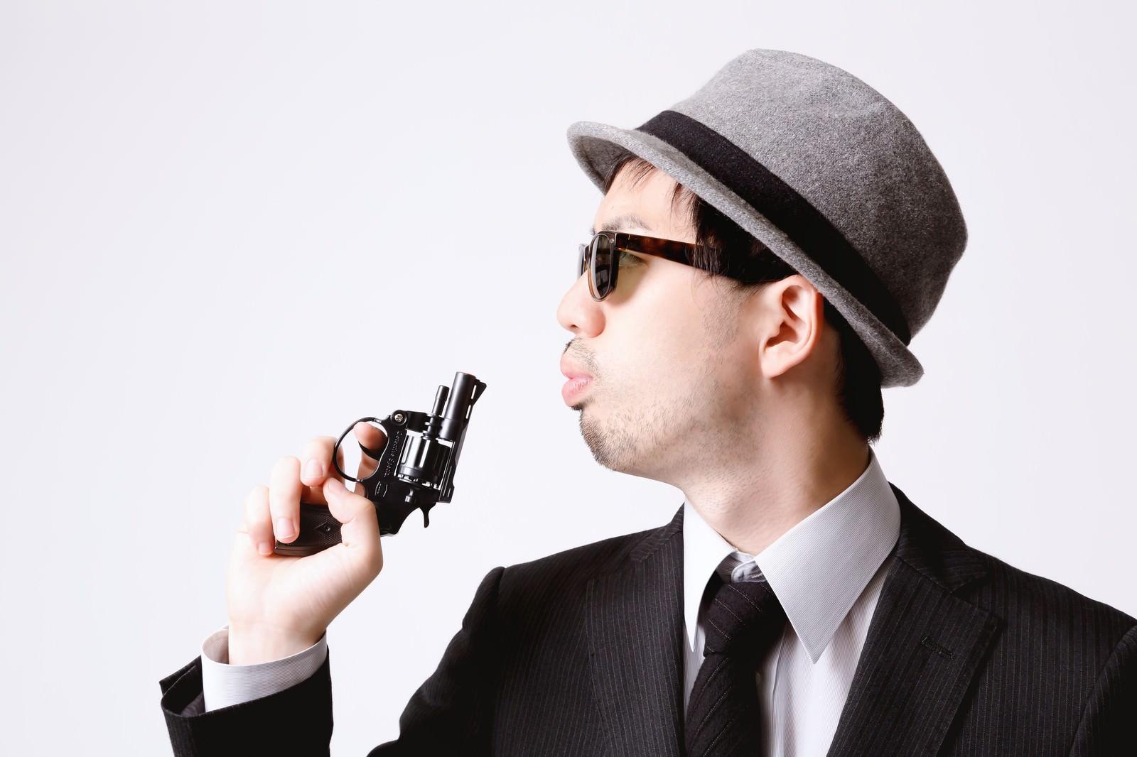 「拳銃の硝煙を吹き消すエージェント」の写真[モデル:ひろゆき]