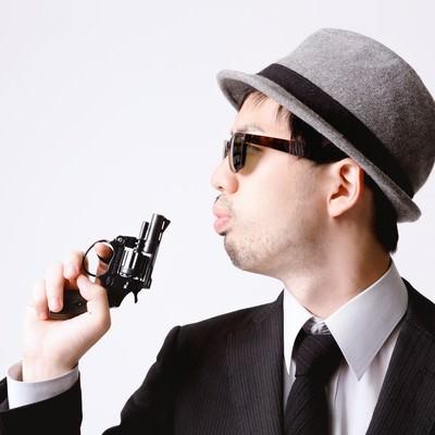 「拳銃の硝煙を吹き消すエージェント」の写真素材
