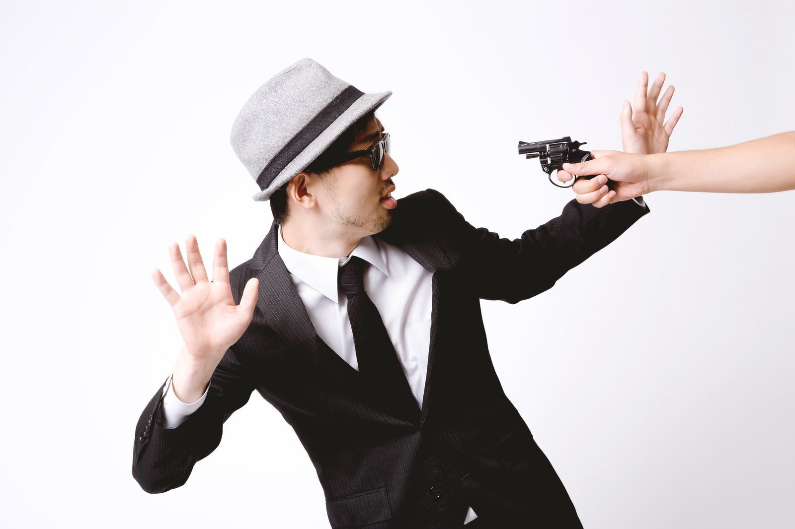 「拳銃を突きつけられ両腕をあげるエージェント」の写真[モデル:ひろゆき]