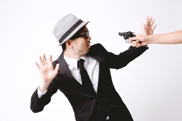 拳銃を突きつけられ両腕をあげるエージェントの写真