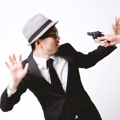 「拳銃を突きつけられ両腕をあげるエージェント」の写真素材