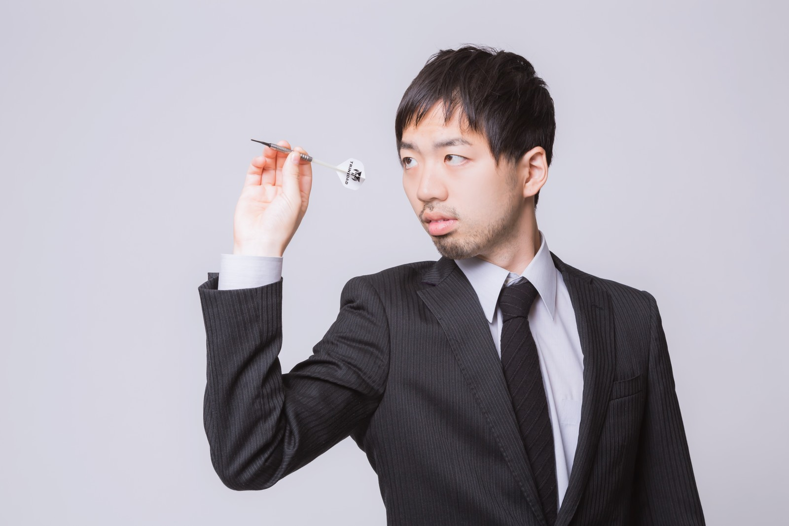 「ダーツをするスーツ姿の男性」の写真[モデル:ひろゆき]