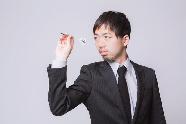 ダーツをするスーツ姿の男性の写真