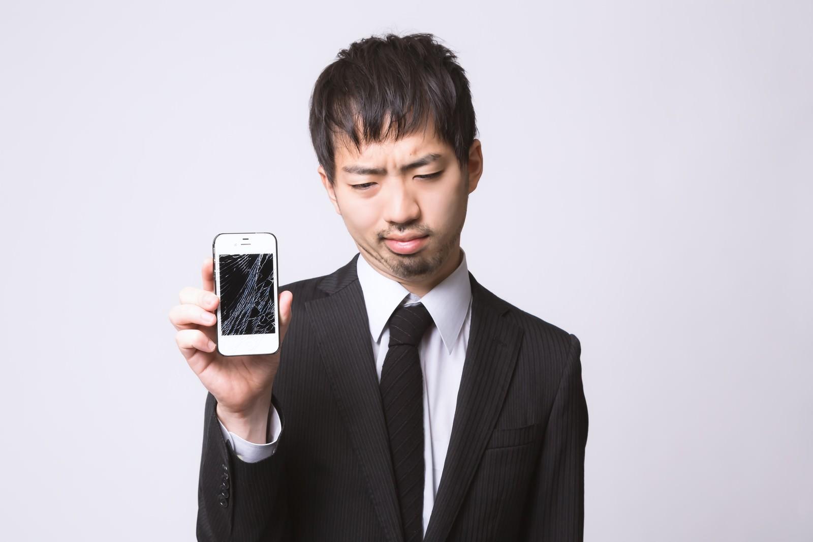 「スマートフォンを落としてガックリしている男性」の写真