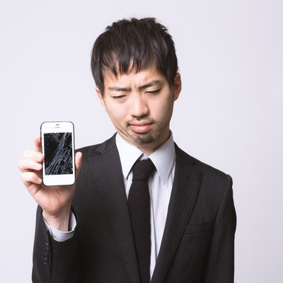 スマートフォンを落としてガックリしている男性の写真