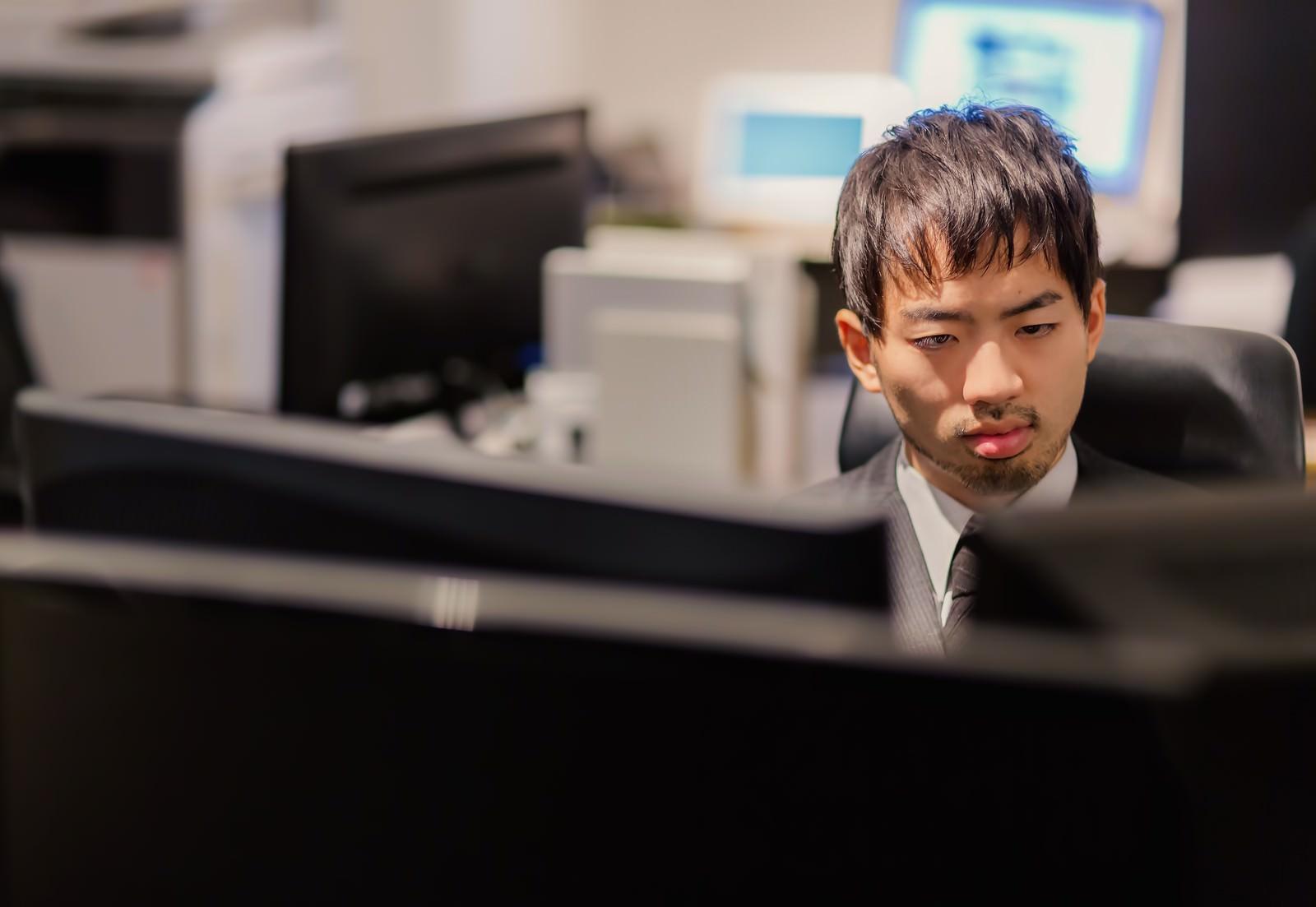 「PCが並ぶオフィスでモニタリングする男性PCが並ぶオフィスでモニタリングする男性」[モデル:ひろゆき]のフリー写真素材を拡大