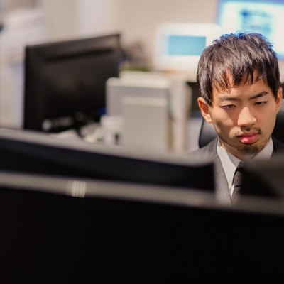 「PCが並ぶオフィスでモニタリングする男性」の写真素材