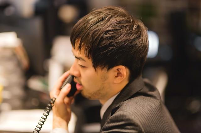 オフィスで電話対応中のビジネスマンの写真
