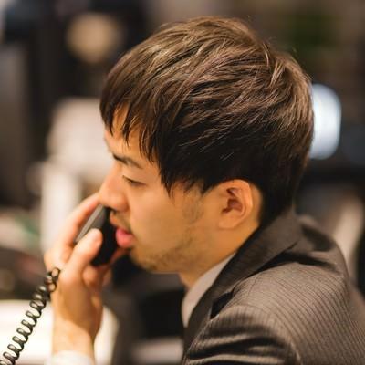 「オフィスで電話対応中のビジネスマン」の写真素材