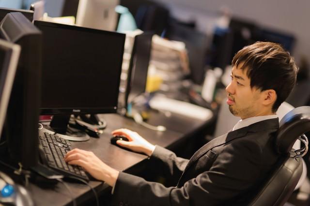 Web制作会社のオフィスで作業するスーツ姿の男性の写真