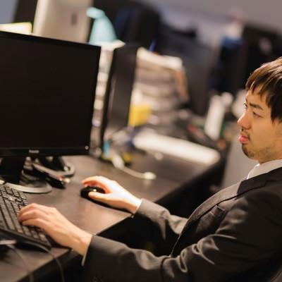 「Web制作会社のオフィスで作業するスーツ姿の男性」の写真素材