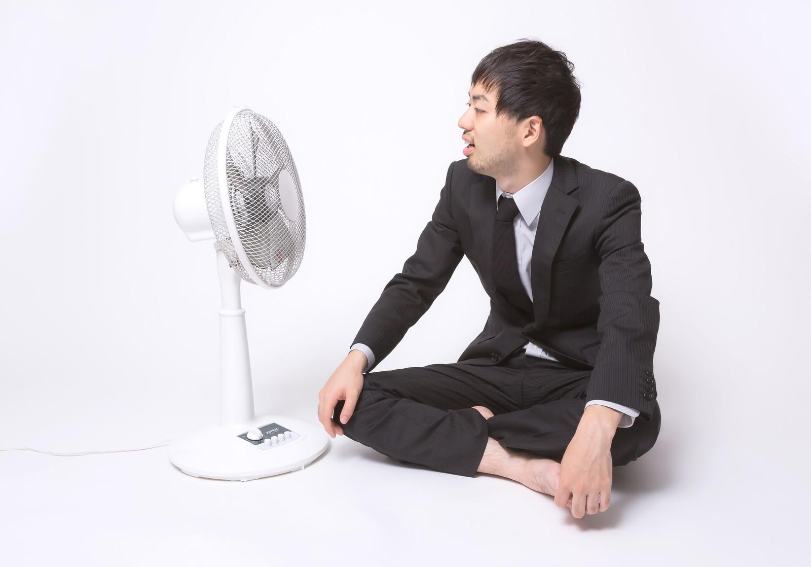 「扇風機の前で涼もうとするサラリーマン」の写真[モデル:ひろゆき]