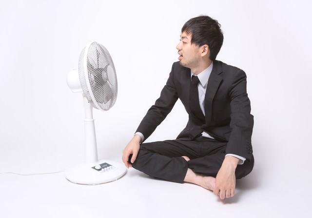 扇風機の前で涼もうとするサラリーマンの写真
