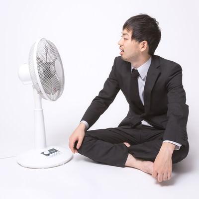 「扇風機の前で涼もうとするサラリーマン」の写真素材