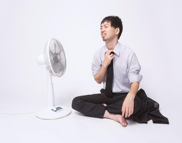 暑すぎて上着を脱いで扇風機に当たる会社員の写真