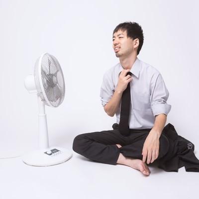 「暑すぎて上着を脱いで扇風機に当たる会社員」の写真素材