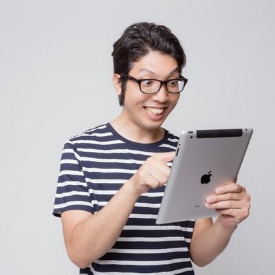 「初めてiPadを使う男性の様子」の写真素材