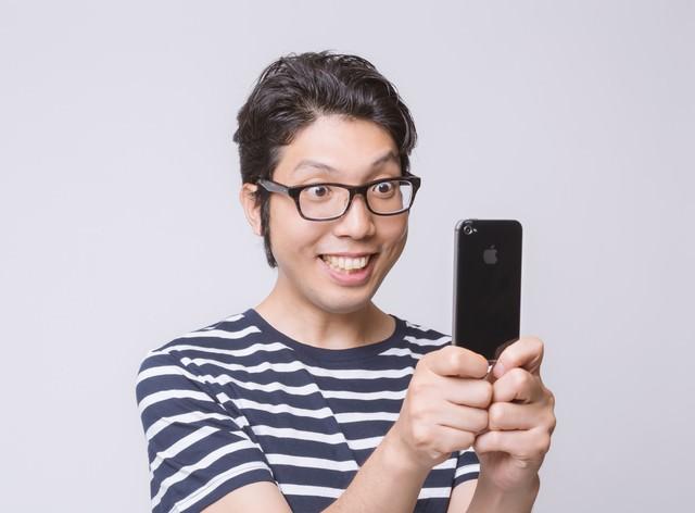 スマートフォンで撮影する男性の写真