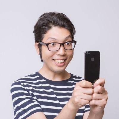 「スマートフォンで撮影する男性」の写真素材