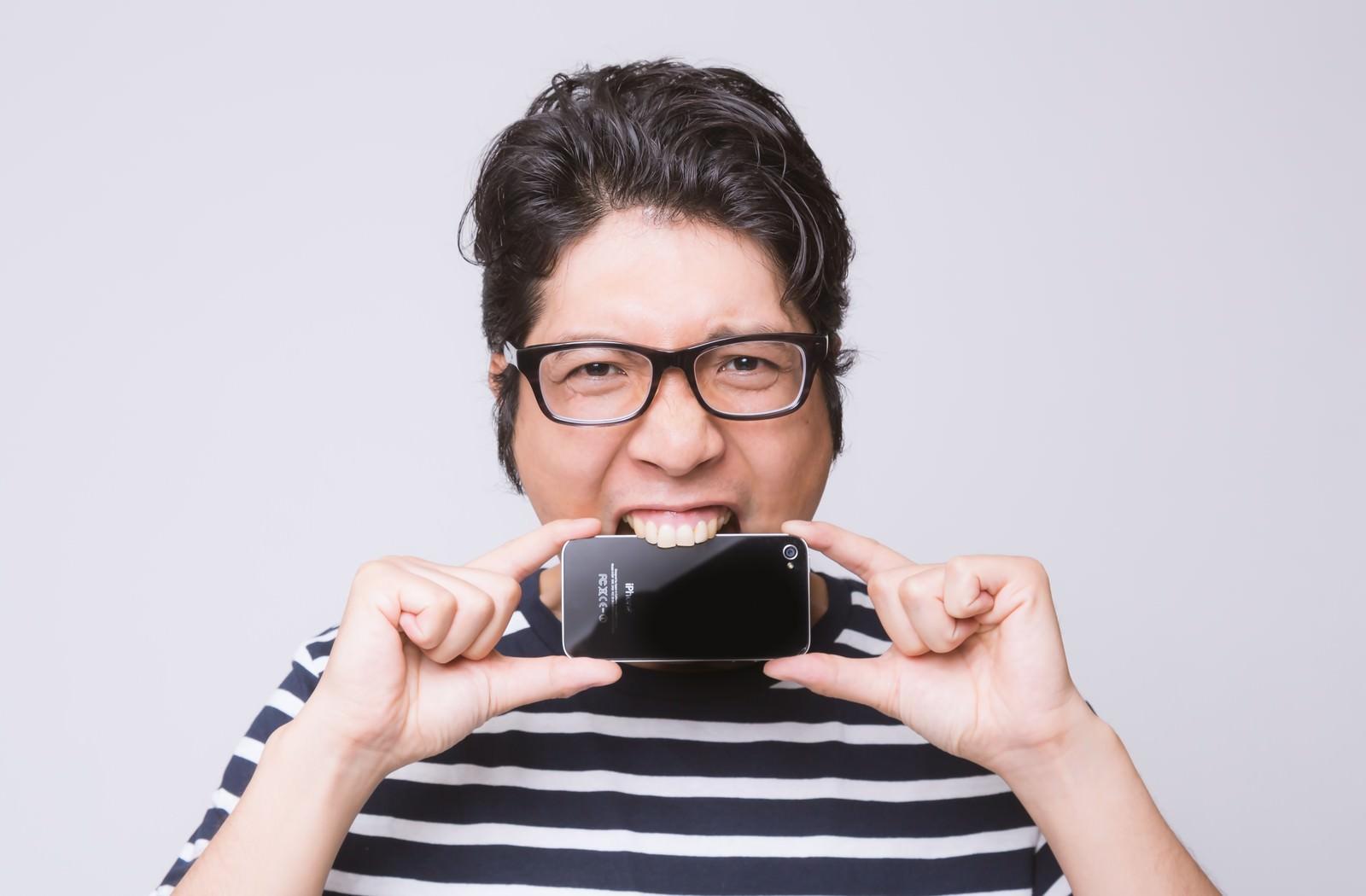 「ストレスからスマートフォンを齧るアプリ開発者」の写真[モデル:紳さん]