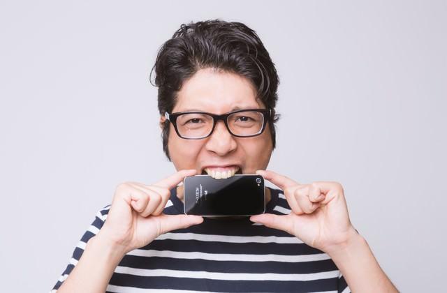 ストレスからスマートフォンを齧るアプリ開発者の写真
