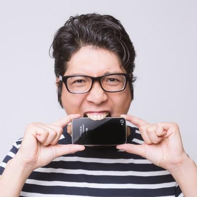 「ストレスからスマートフォンを齧るアプリ開発者」の写真素材