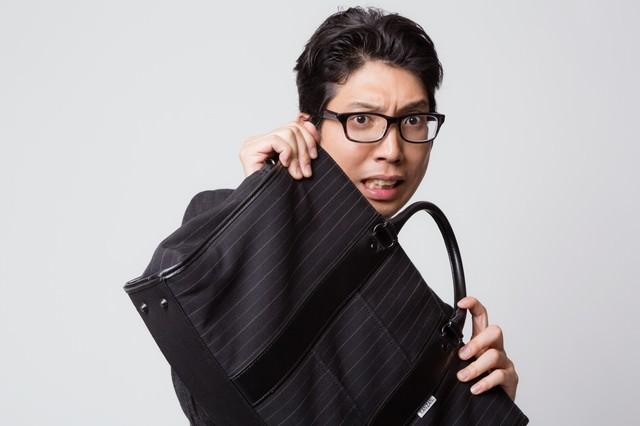 鞄でガード(防御)する怯えた表情のビジネスマンの写真