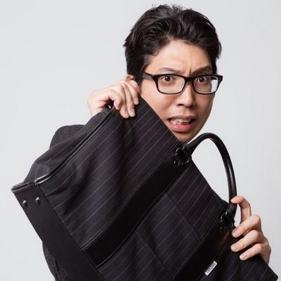 「鞄でガード(防御)する怯えた表情のビジネスマン」の写真素材