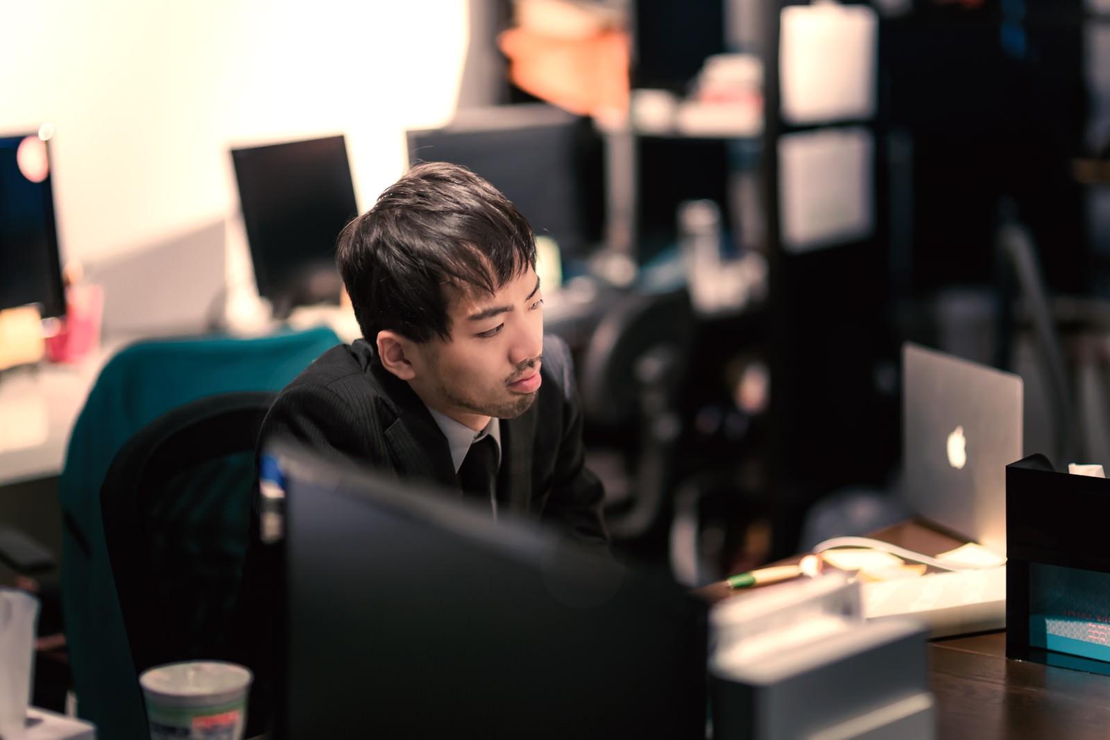 「オフィスで孤独に残業中」の写真[モデル:ひろゆき]