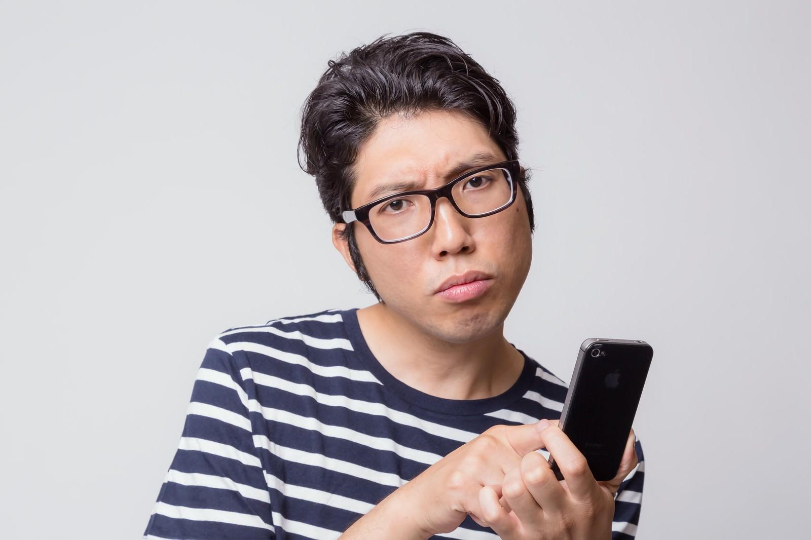 「アプリの使い方がわからなくて困惑する男性」[モデル:紳さん]