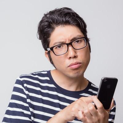 「アプリの使い方がわからなくて困惑する男性」の写真素材