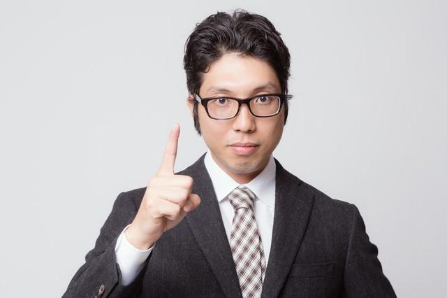 「ナンバーワンです」と人差し指を立てるビジネスマンの写真