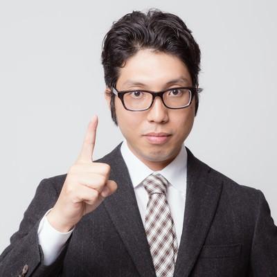 「「ナンバーワンです」と人差し指を立てるビジネスマン」の写真素材